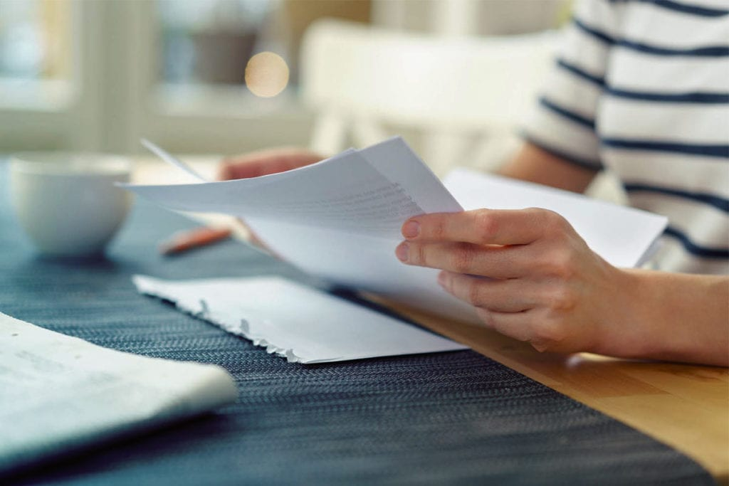 Büroangestellte liest einen geöffneten Brief. Briefe digital versenden und in Papierform erhalten mit Binect.