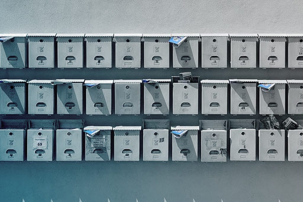 Drei Reihen Briefkästen an einer Hauswand.