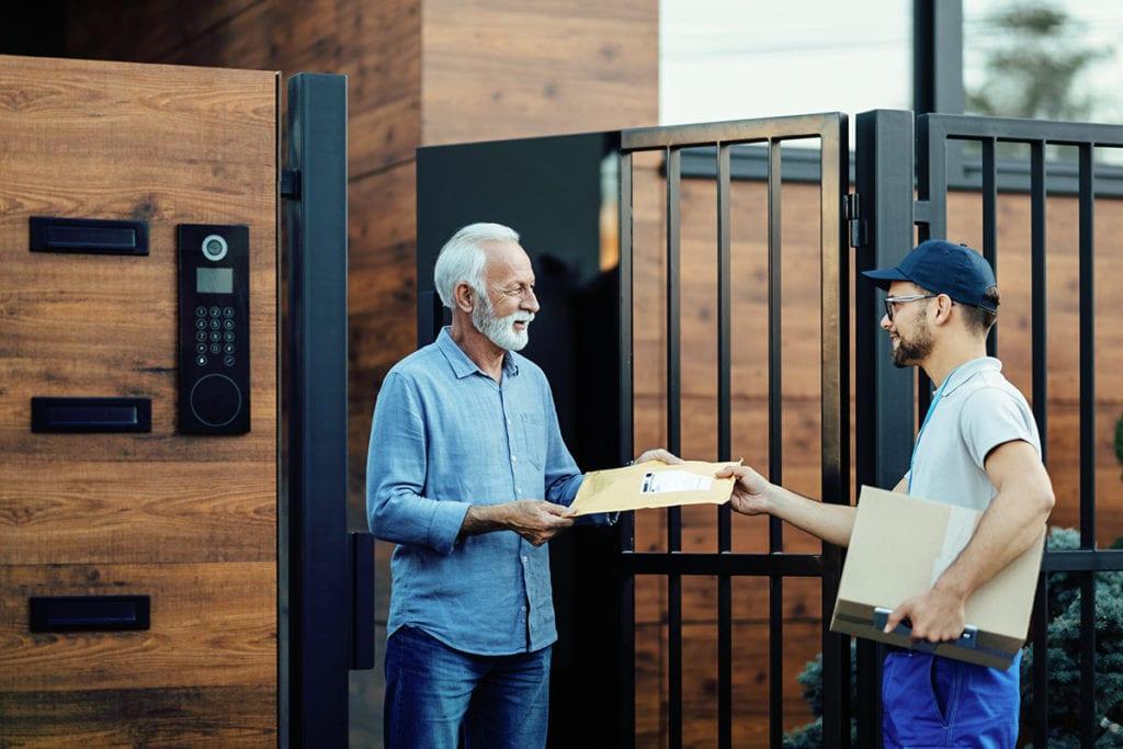 PZA/PZU wurde digital über Binect versendet. Ein älterer Mann nimmt am Tor seines Grundstücks einen Postzustellungsauftrag vom Kurierdienst entgegen.