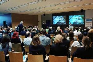 Jürgen Kneißl hält einen Vortrag zur digitalen Poststelle vor großem Publikum.