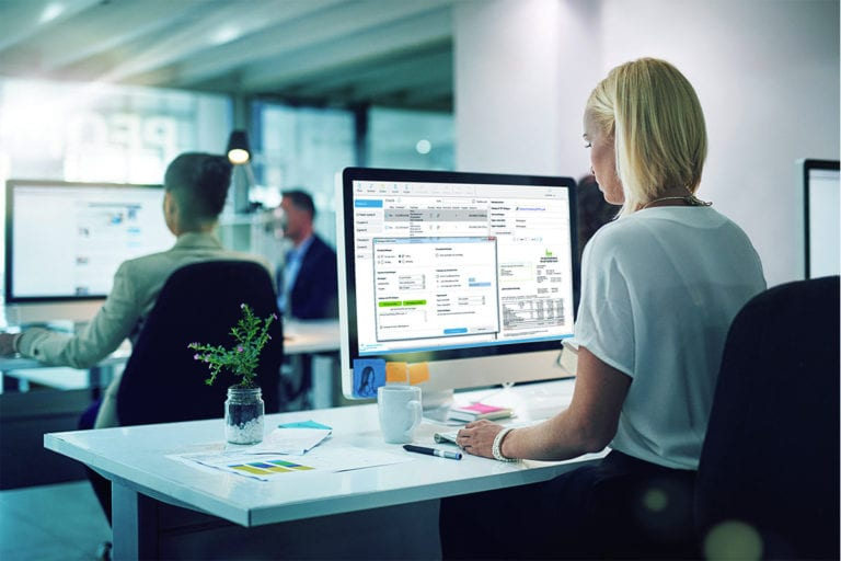Junge Büroangestellte versendet Briefe digital am Computer in einem Großraumbüro.