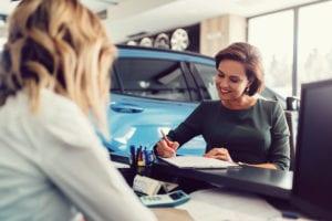 Eine Frau unterschreibt einen Kaufvertrag für ein Auto.