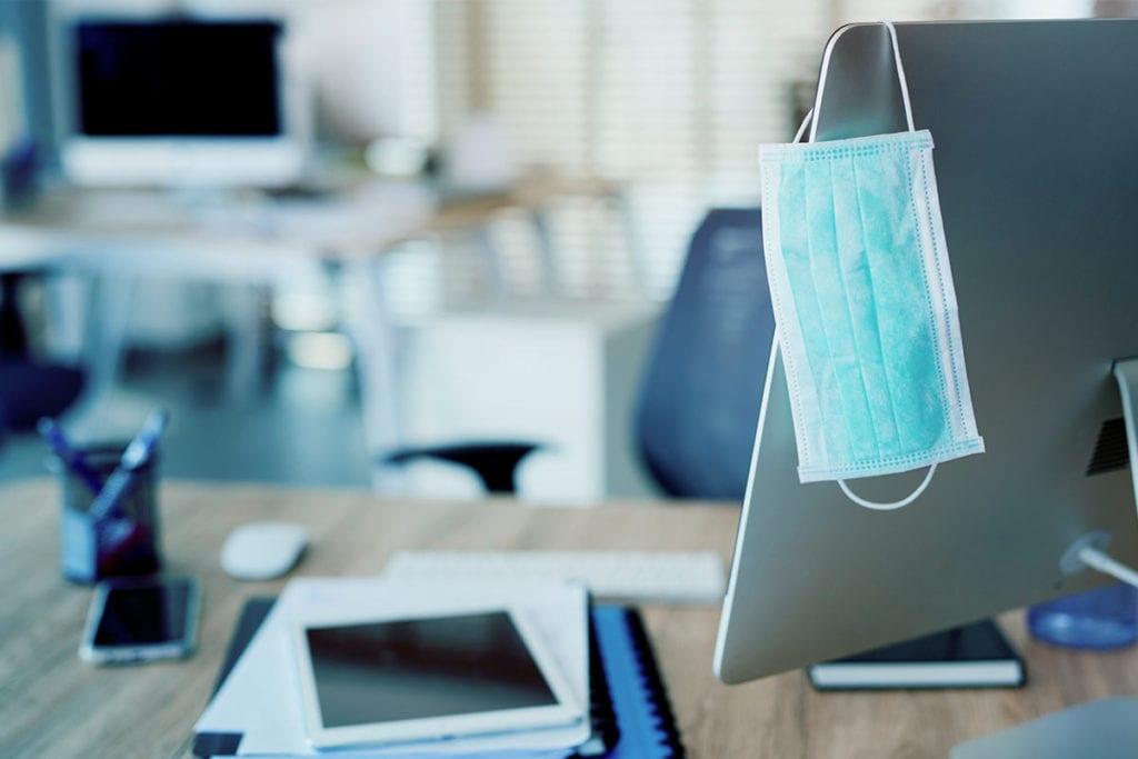 Eine Mund-Nasenschutz-Maske hängt an einem Bildschirm in einem leeren Büro.