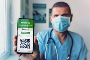 Seinen digitalen Impfnachweis zeigt ein Arzt mit Mund-Nasen-Schutz auf seinem Smartphone.